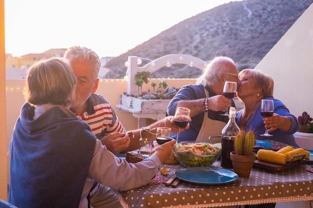 Grupo de idosos se divertindo celebrando um evento como o feriado ou ano novo nas férias ao ar livre no terraço com vista para a cidade e para o mar