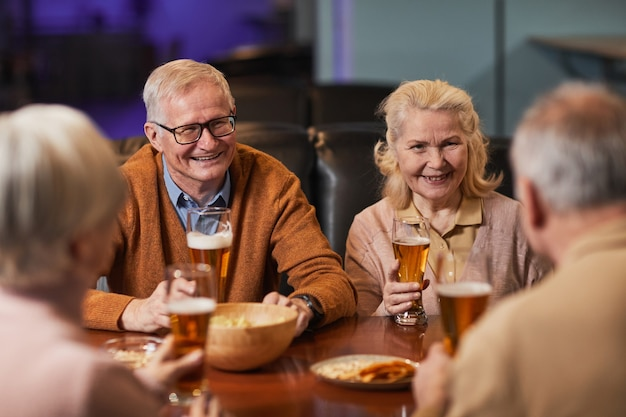 Grupo de idosos sorridentes bebendo cerveja em um bar enquanto se divertem à noite com os amigos, copie o espaço