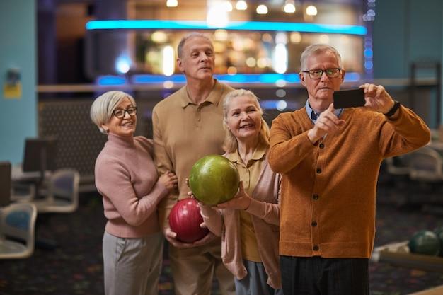 Grupo de idosos tirando fotos de selfie jogando boliche e se divertindo na pista de boliche