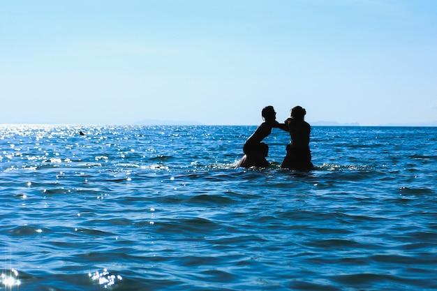 Grupo de imagem de silhueta jovens estão jogando no mar