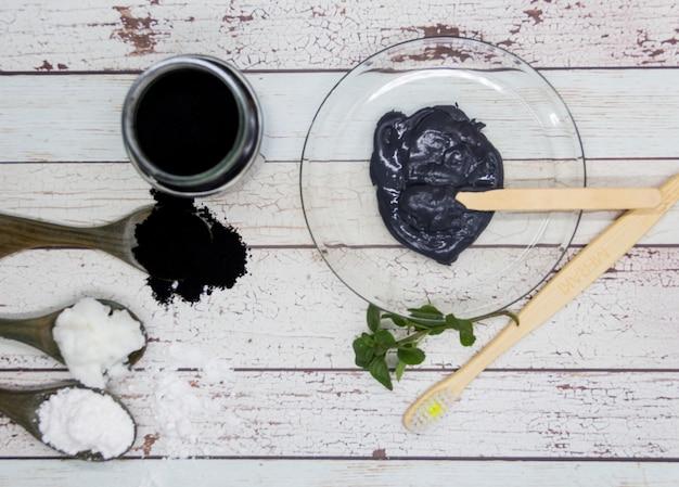 Grupo de ingredientes naturais para preparar pasta de dente com carvão ativado.
