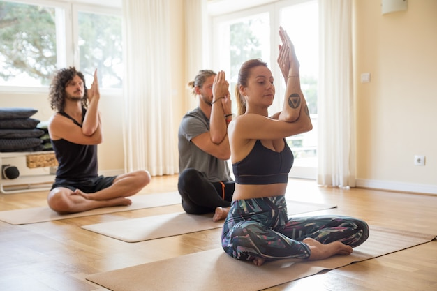 Grupo de iogues focados desfrutando de aulas dentro de casa