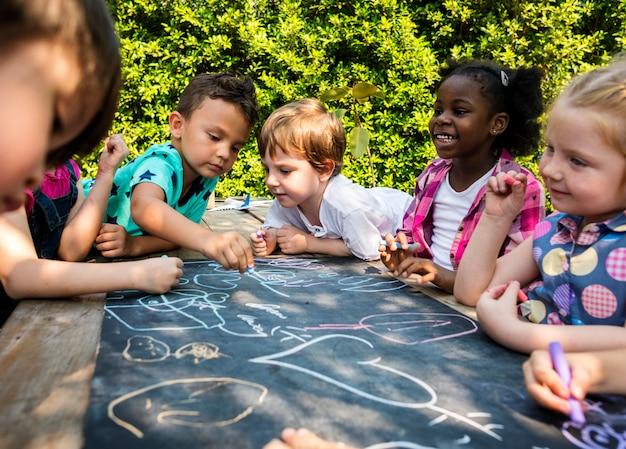 Grupo de jardim de infância crianças amigos desenho aula de arte ao ar livre