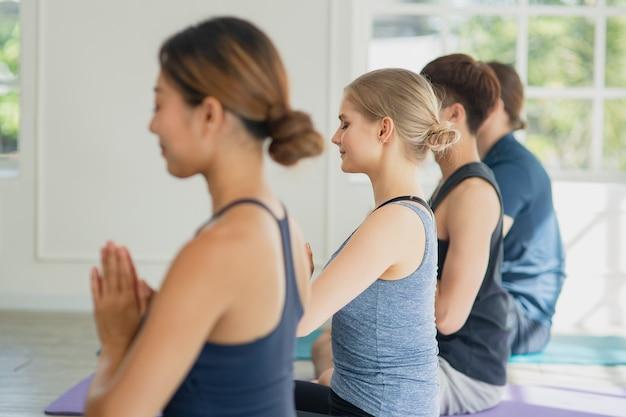Grupo de jovem amigo multiétnico fazendo exercícios e praticando ioga para treinar meditando juntos