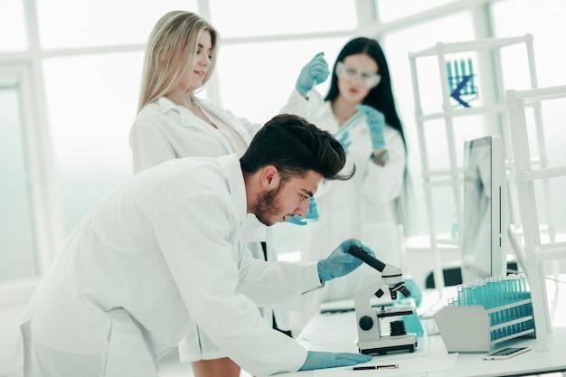 Grupo de jovem cientista fazendo experiências em laboratório