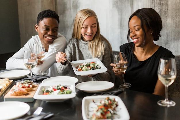 Grupo de jovens a jantar juntos