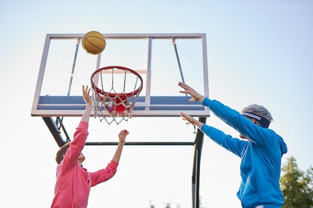 Grupo de jovens adolescentes do sexo masculino com capuzes coloridos jogando basquete ao ar livre na rua