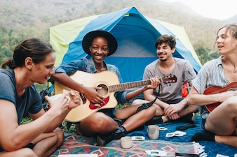 Grupo de jovens adultos amigos no acampamento tocando violão e ukelele e cantando juntos