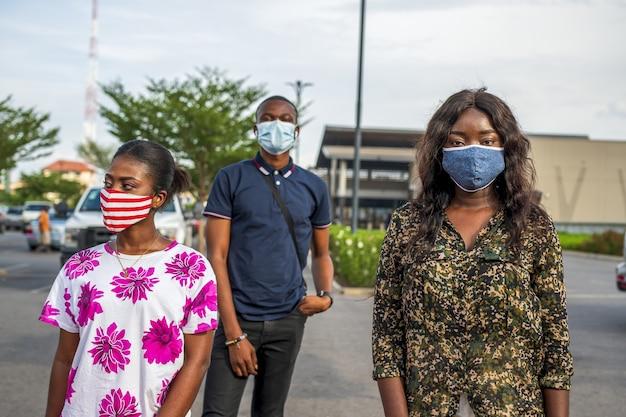 Grupo de jovens africanos com máscaras em pé na rua