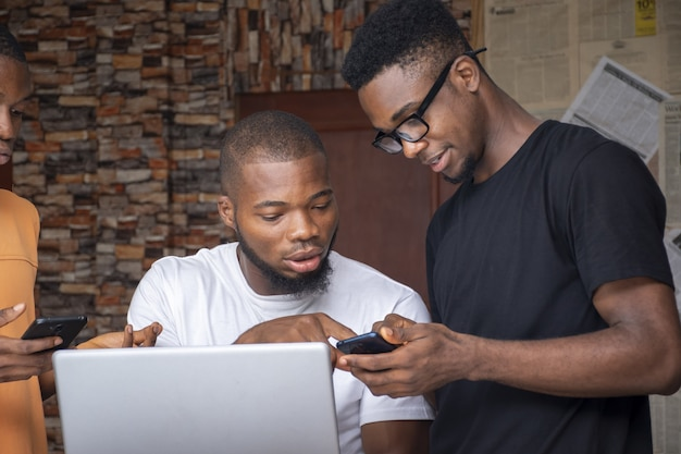 Grupo de jovens africanos discutindo um projeto enquanto usam seus laptops e telefones
