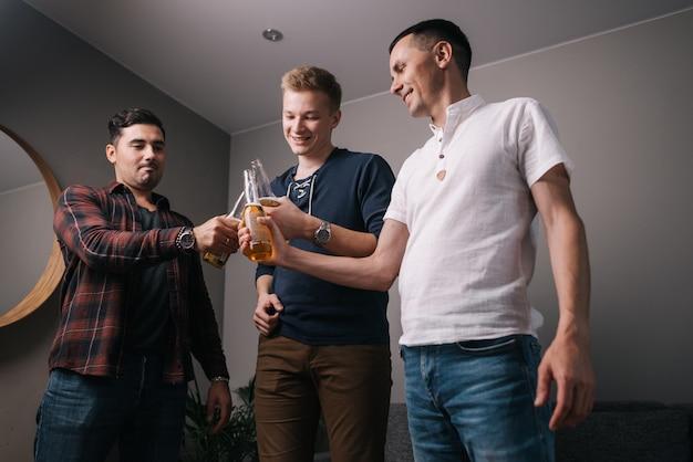 Grupo de jovens alegres batendo garrafas de cerveja