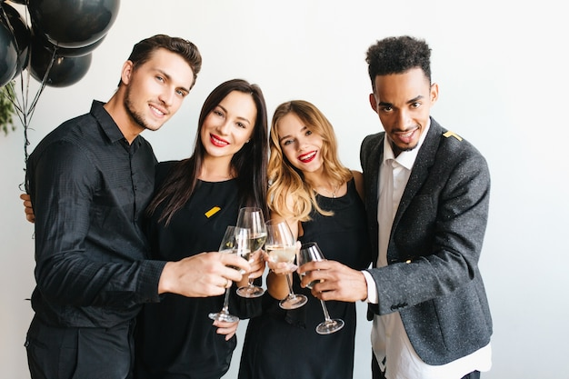 Grupo de jovens alegres em trajes da moda levantando taças com champanhe