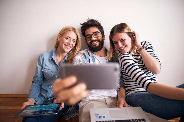 Grupo de jovens alegres está posando para uma selfie enquanto está sentado no chão encostado na parede.