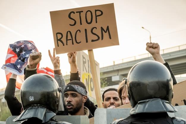 Grupo de jovens americanos descontentes erguendo os punhos e estandarte enquanto pedem para parar o racismo, a polícia mantendo a multidão