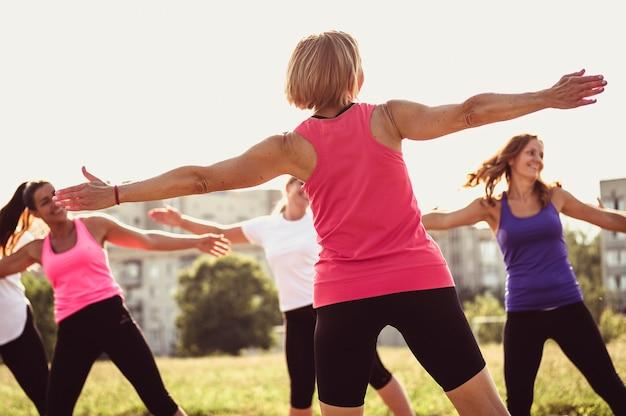 Grupo de jovens amigas exercitando em um parque