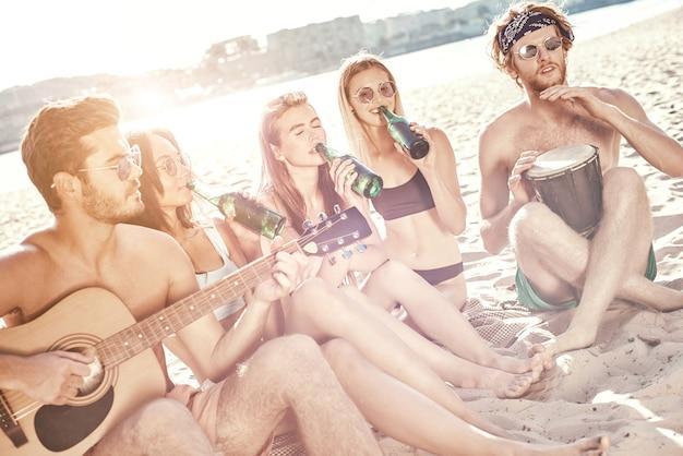 Grupo de jovens amigas sentadas na praia, em espreguiçadeiras, cantando e tocando violão, desfrutando do pôr do sol
