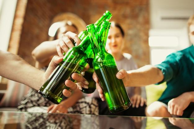 Grupo de jovens amigos a bater garrafas de cerveja, a divertir-se e a festejar juntos