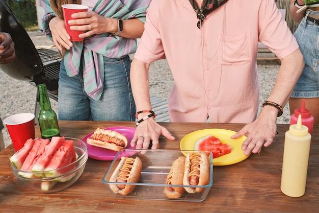 Grupo de jovens amigos a comer snacks junto à mesa de madeira