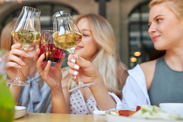 Grupo de jovens amigos a tilintar de copos com bebidas num café