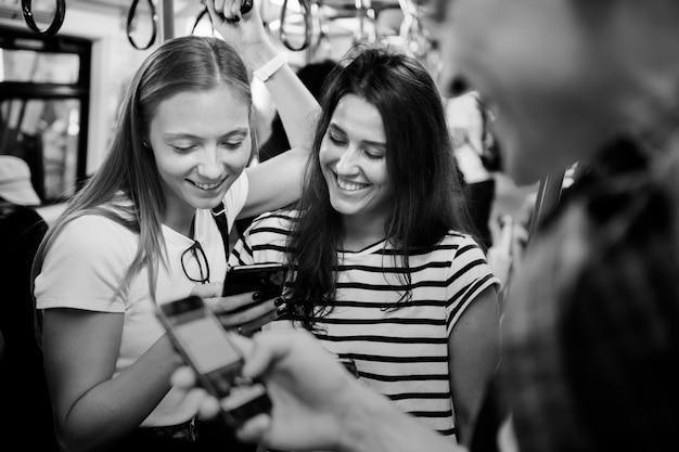 Grupo de jovens amigos adultos usando smartphones no metrô