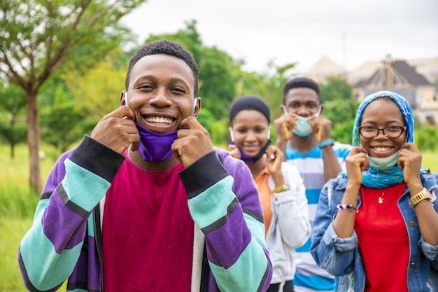 Grupo de jovens amigos africanos alegres usando máscaras e distanciamento social em um parque