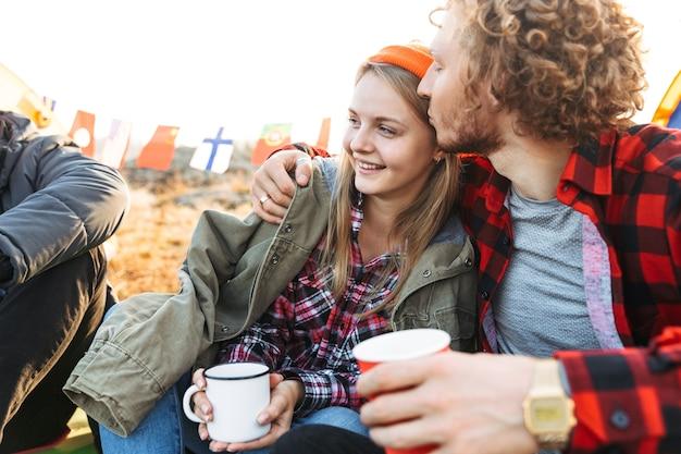 Grupo de jovens amigos alegres acampando ao ar livre, sentados com xícaras e garrafa térmica