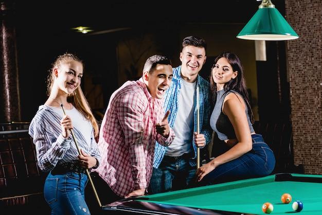 Grupo de jovens amigos alegres jogando bilhar.