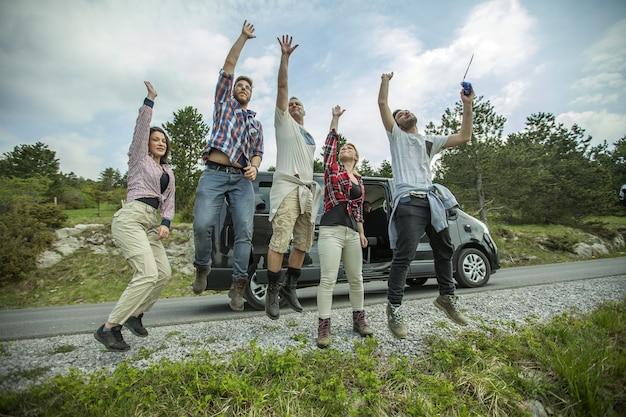 Grupo de jovens amigos alegres pulando e se divertindo ao ar livre na estrada