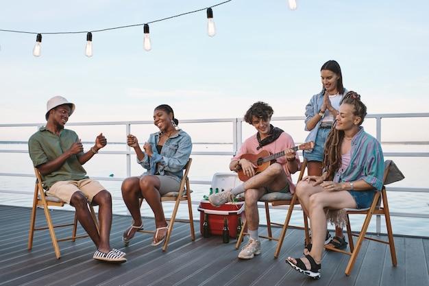 Grupo de jovens amigos alegres relaxando no cais
