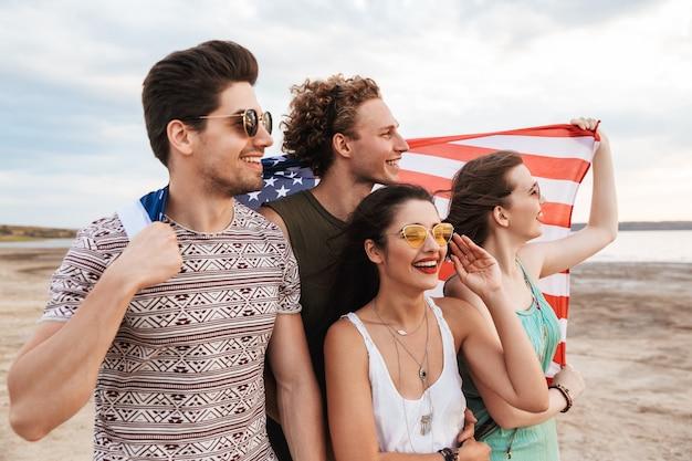 Grupo de jovens amigos alegres se divertindo na praia, segurando a bandeira dos estados unidos