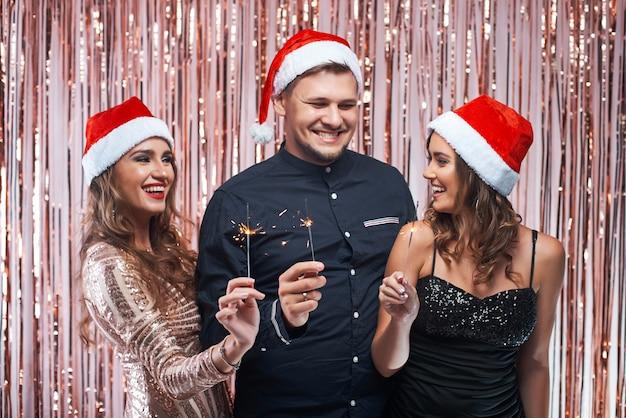 Grupo de jovens amigos, aproveitando a celebração do ano novo com brilhos nas mãos.