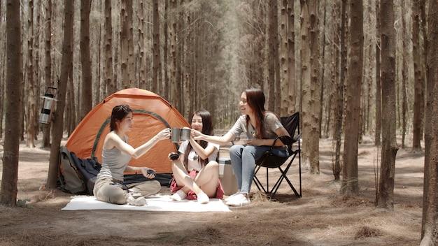 Grupo de jovens amigos asiáticos acampar ou fazer um piquenique juntos na floresta