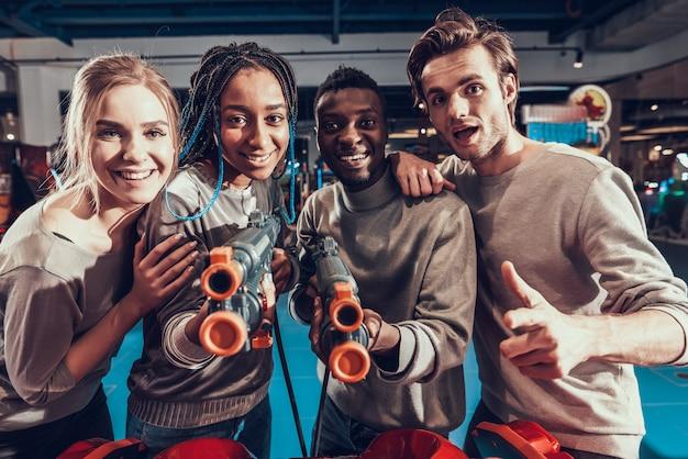 Grupo de jovens amigos atirando armas no arcade.