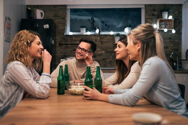 Grupo de jovens amigos brindando com bebidas em casa.