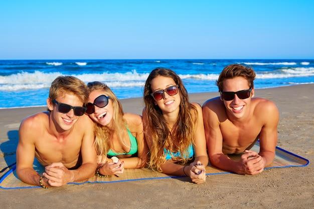 Grupo de jovens amigos casais retrato na praia