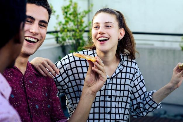 Grupo de jovens amigos com pizza e garrafas de bebida
