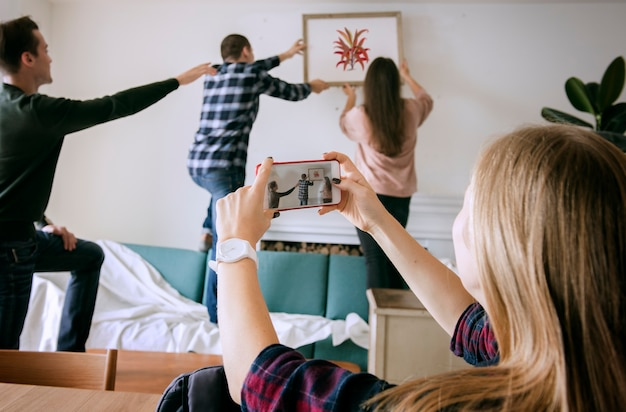Grupo de jovens amigos de decorar o apartamento e uma mulher tirando uma foto