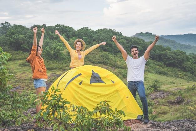 Grupo de jovens amigos de diversidade goza e mãos levantadas acampar na floresta nas férias de férias no verão, viagens de aventura
