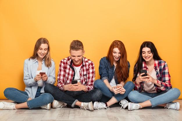 Grupo de jovens amigos de escola alegres usando telefones celulares