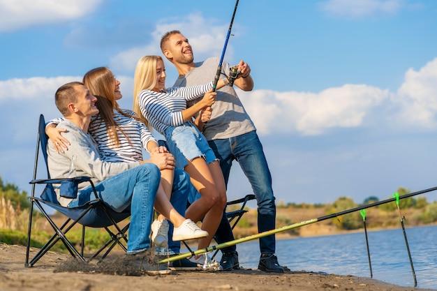 Grupo de jovens amigos de pesca no cais à beira do lago