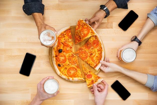 Grupo de jovens amigos degustando pizza e bebendo cerveja na mesa de madeira
