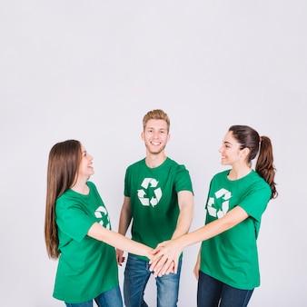 Grupo de jovens amigos felizes empilhando suas mãos
