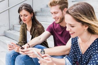 Grupo de jovens amigos felizes usando telefone celular
