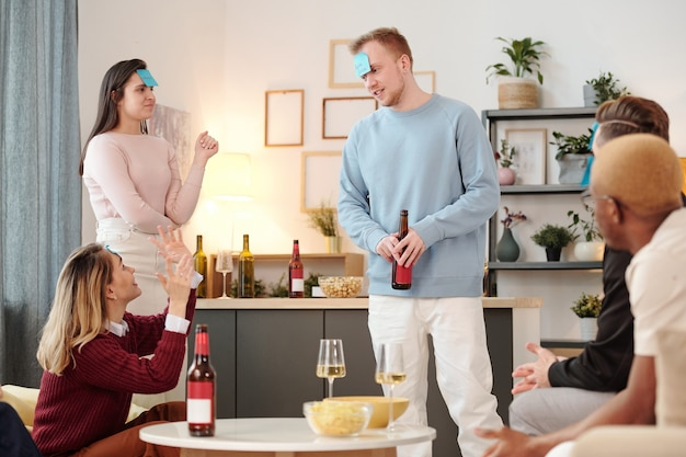 Grupo de jovens amigos interculturais alegres em trajes casuais elegantes, sentados à pequena mesa redonda branca na sala de estar, comendo pizza e bebendo