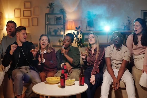 Grupo de jovens amigos interculturais sentados em um sofá comprido ao lado de uma mesinha com lanches e bebidas e cantando no karaokê na sala de estar