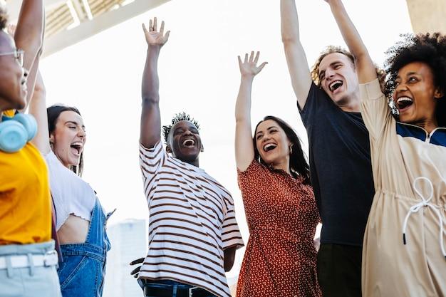 Grupo de jovens amigos levantando as mãos em união
