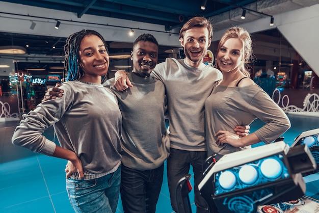 Grupo de jovens amigos que pilotam naves espaciais na arcada.
