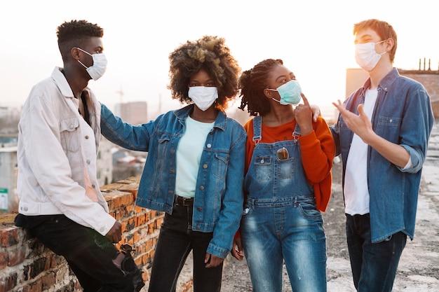 Grupo de jovens amigos saindo com máscaras médicas
