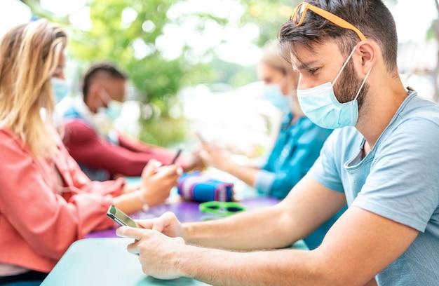 Grupo de jovens amigos usando o aplicativo de rastreamento em telefones móveis