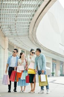 Grupo de jovens animados com sacolas de compras em pé na rua de um vilarejo comercial